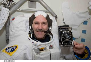 Astronaut John Grunsfeld holds Bradford Washburn's camera on a recent mission to repair the Hubble Telescope