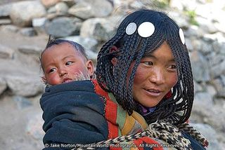 TD-GM-1000: 	A drokpa, or Tibetan nomad, woman with her baby tied to her back outside of Ditrul Phuk Gompa on the kora, or circumabulation, of Mount Kailash, Tibet.